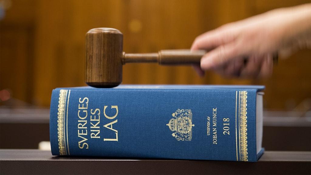 En blå lagbok ligger på ett bod och en klubba hålls i en hand.