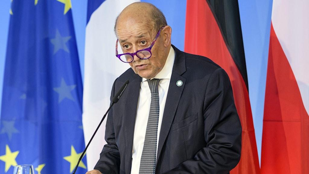 Äldre skallig man med glasögonen på näsan och klädd i mörk kostym och slips står på podium med flaggor i bakgrunden.