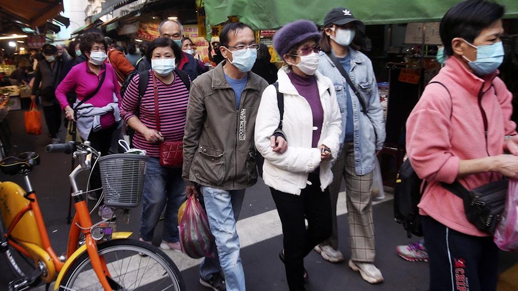 Personer på gata i Taiwan med munskydd.