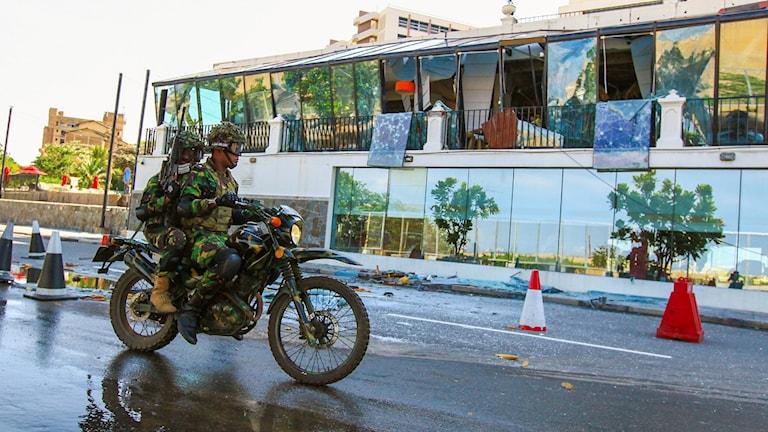 Motorcyklist passerar det bombade  Kingsbury Hotel i Colombo, Sri Lanka.