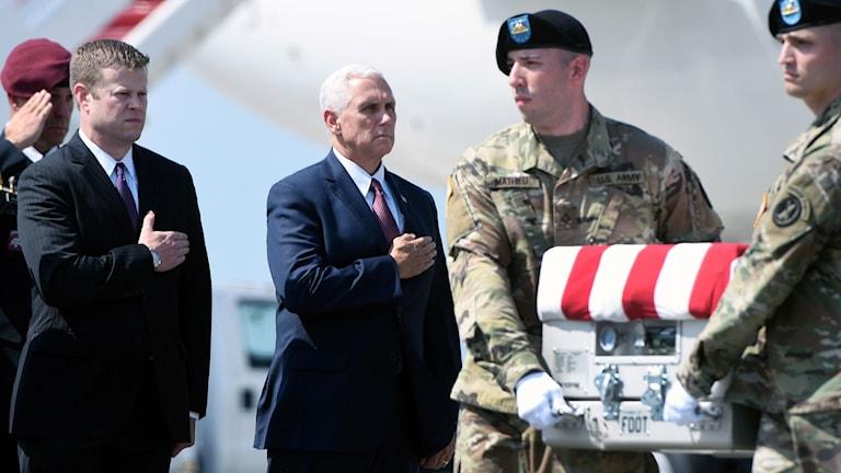 USA:s vicepresident Mike Pence håller handen över hjärtat i samband med att kvarlevorna efter en stupad soldat anländer till en militärbas.