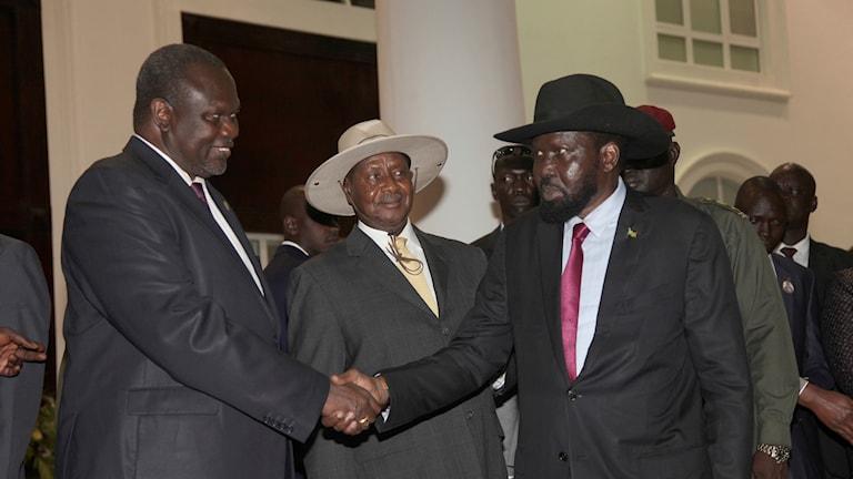 Vicepresident Riek Machar till vänster, Ugandas president Yoweri Museveni och president Salva Kiir till höger skakar hand efter att ha skrivit under avtalet.