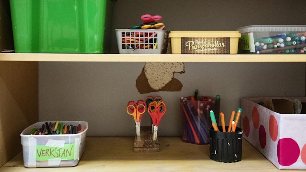 Två hyllplan med skolmaterial som pennor och saxar.