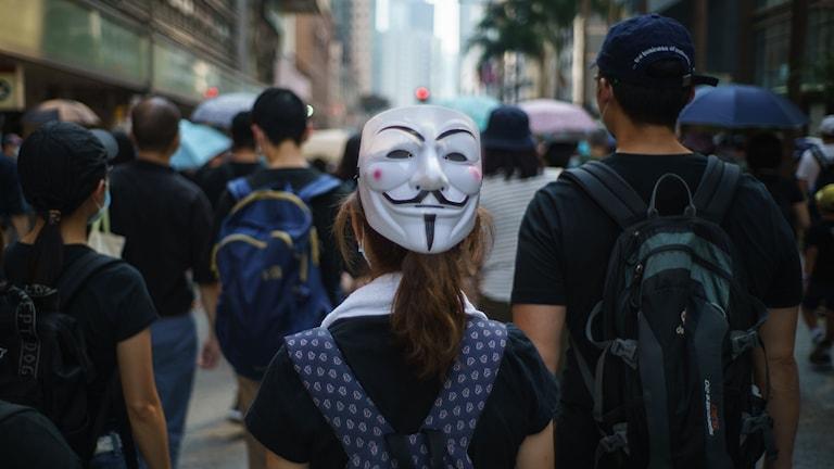 En demonstrant bär en Guy Fawkes-mask på bakhuvudet.