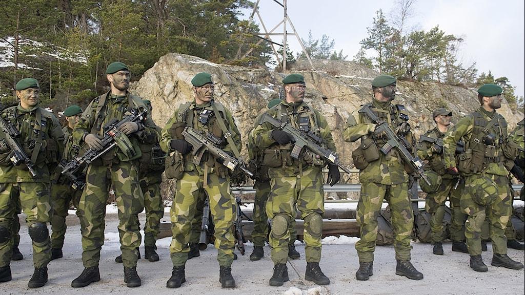 Militärer med vapen.