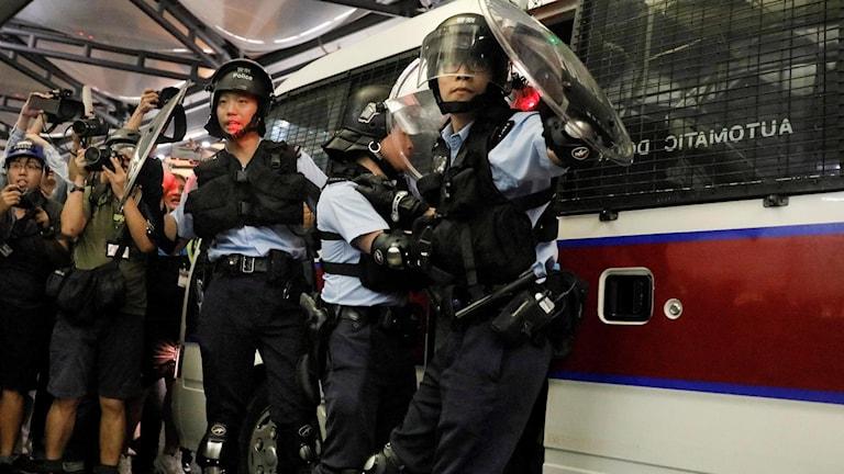 Polis flyttar gripna demonstranter.