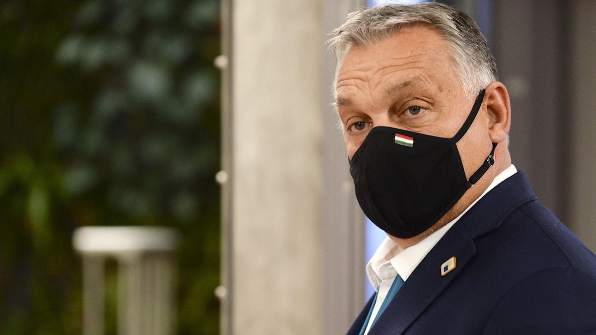 En man står upp med munskydd på sig