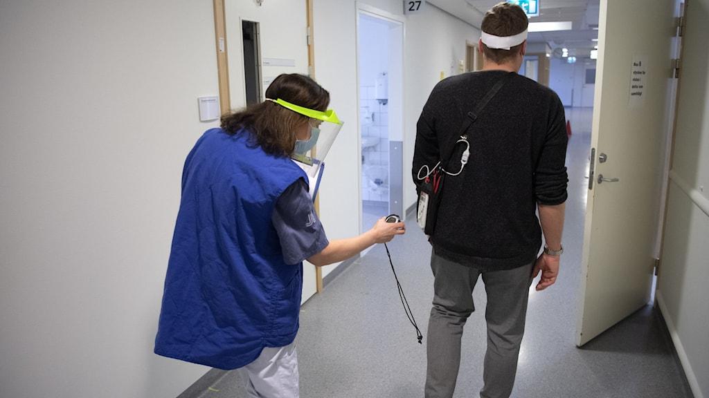 Fysioterapeut på Karolinska sjukhuset genomför ett gångtest på en patient.