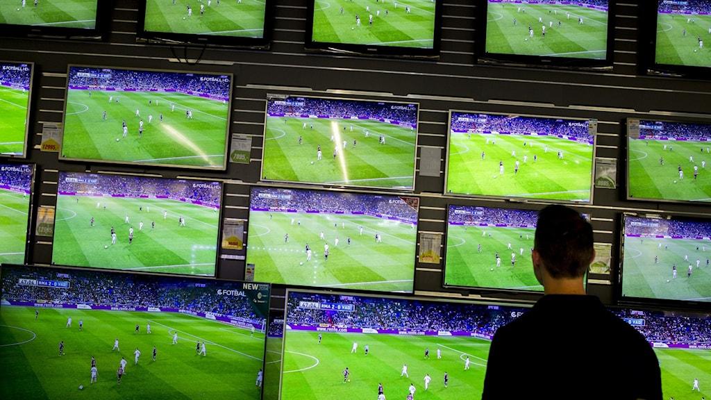Flera tv-apparater längs en väg i butik.