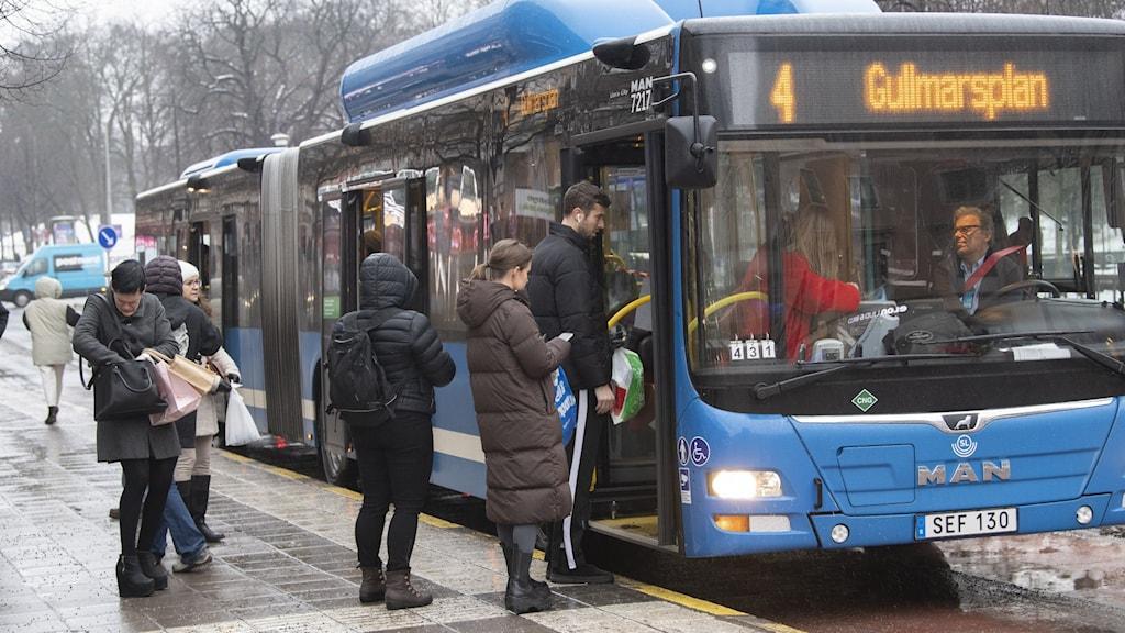 Blå buss vid hållplats och passagerare i kö för att stiga på.