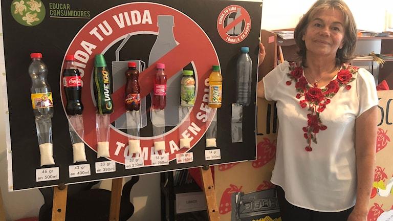Esperanza Cerón med en utbildningsskylt som visar hur mycket socker olika läsk- och juicedrycker innehåller.