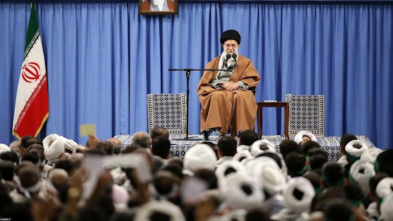Ayatollah Khamenei på en scen framför åhörare.