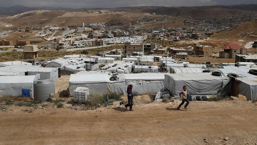 två barn springer utanför ett flyktingläger för syrier i Libanon