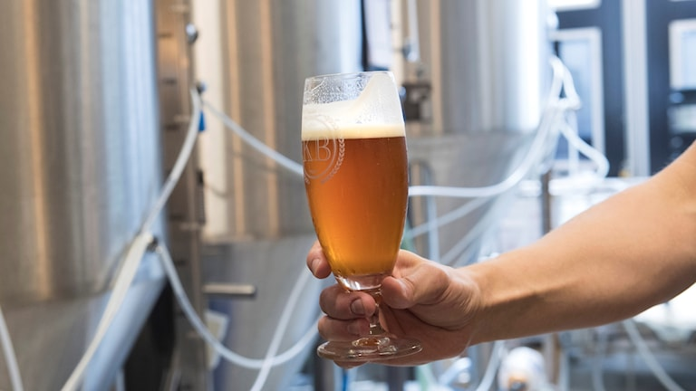 Hand håller ett ölglas i ett bryggeri.