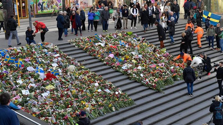 Stockholmers leave flowers at Sergels torg.
