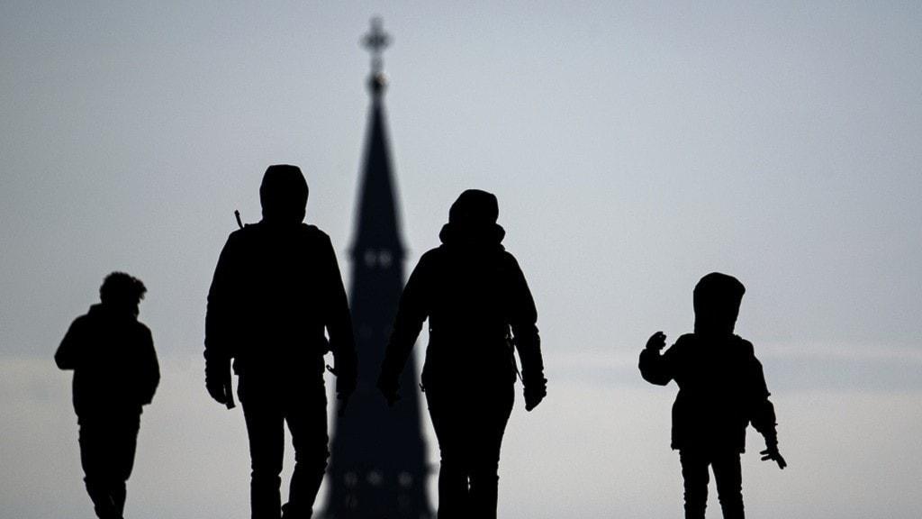 En familj med en kyrka i bakgrunden.