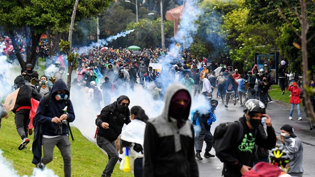 Folk på gata med rök från smällare och allmänt tumult.