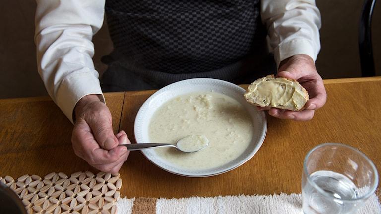 Äldre person äter soppa med smörgås.