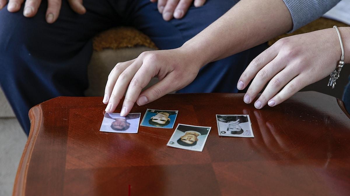 person lägger fotografier på ett bord