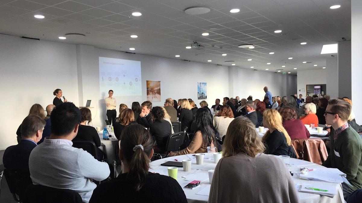 Bilden visar människor på en konferens på Malmömässan. De sitter vid olika bord. Foto: Anna Bubenko/Sveriges Radio.