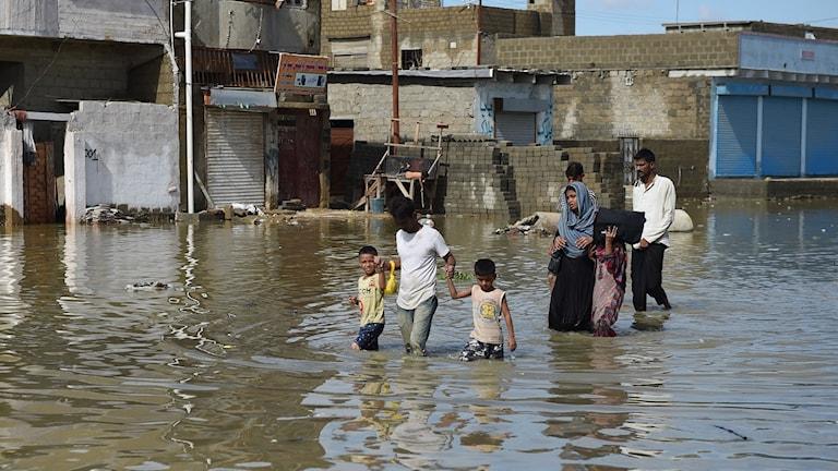 Människor går i vatten framför byggnader.