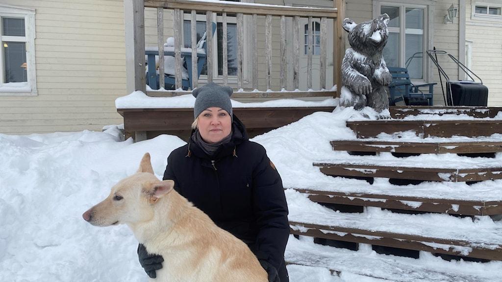 Kvinna framför hus med snö omkring, Hanna Kunnari, företagare, Haparanda.