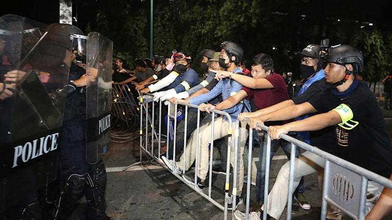 Demonstranter vid kravallstaket.