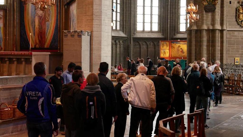 Folk står i kö i en kyrka