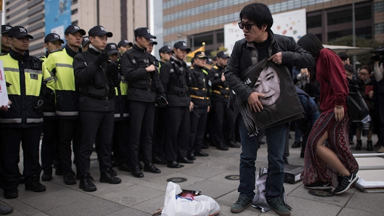 En man håller en bild av Sydkoreas president Park Geun-hye under en demonstration i Seoul.