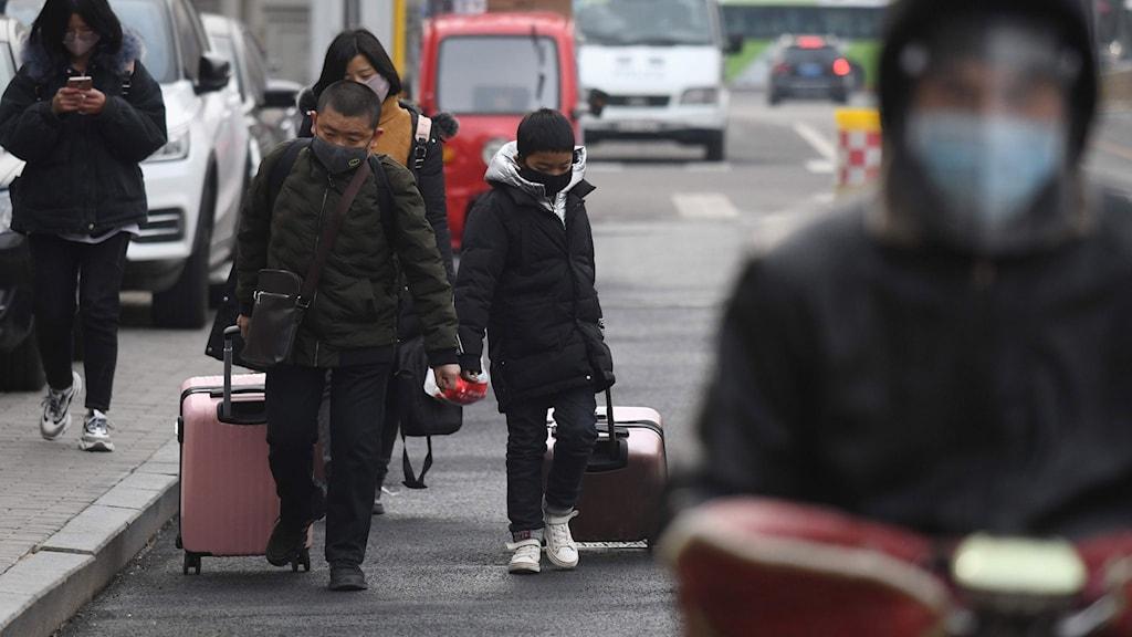 Människor bär ansiktsmask i Peking, 24 februari 2020. Foto: GREG BAKER/TT.