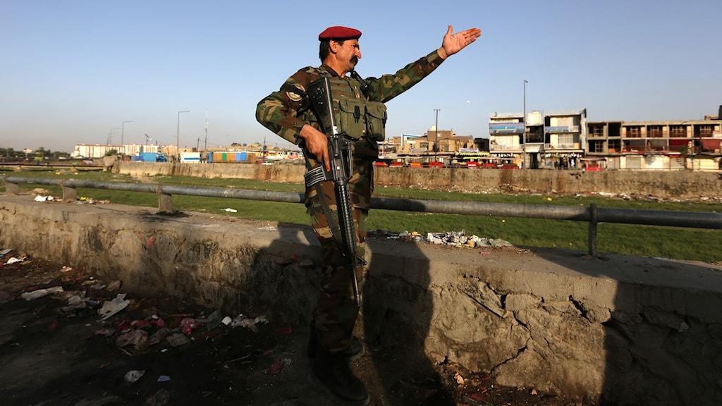 En afghansk soldat inspekterar platsen för självmordsattack i Kabul nära Afghanistans försvarsdepartementet.