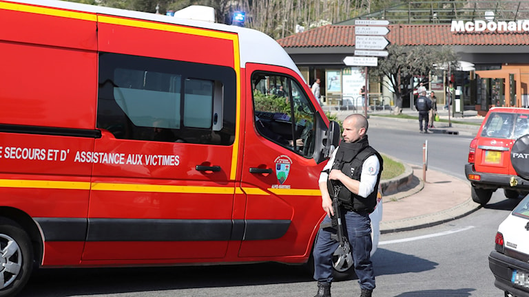 En polisman dirigerar trafik utanför gymnasiet i Grasse där en elev ska ha öppnat eld och skadat åtta personer.