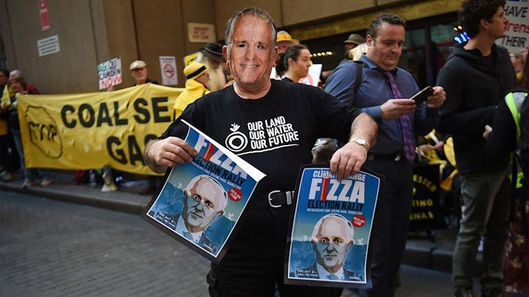 En demonstrant bär en mask föreställande premiärminister Malcolm Turbull.