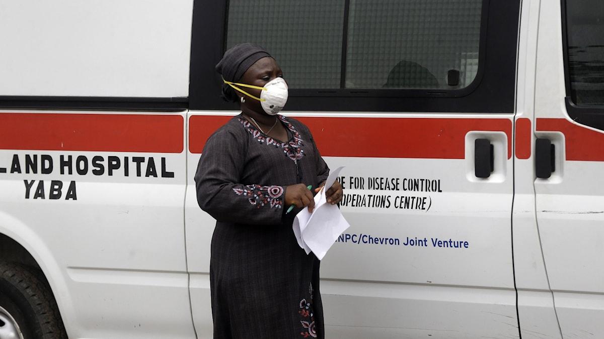 En kvinna med munskydd framför en ambulans i Nigeria.