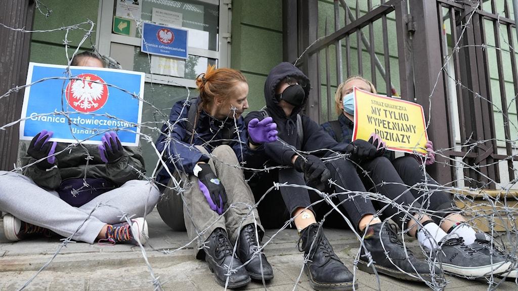 Fyra demonstranter mot behandlingen av migranter i Polen.