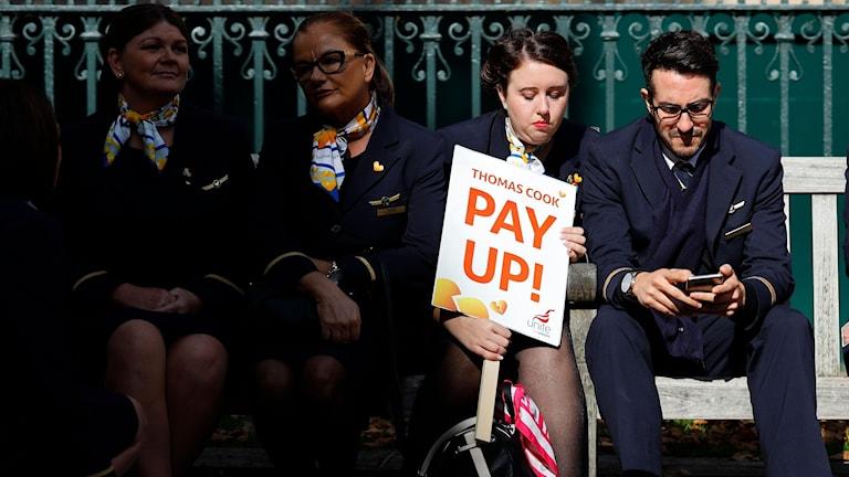 """Flygvärdinnor med plakat där det står """"Pay up"""" sitter på bänk."""