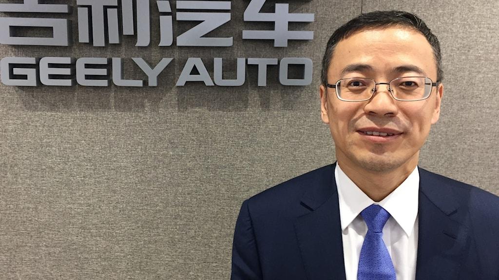 Geelys finanschef Daniel Li framför Geelys logga inne på ett konferensrum