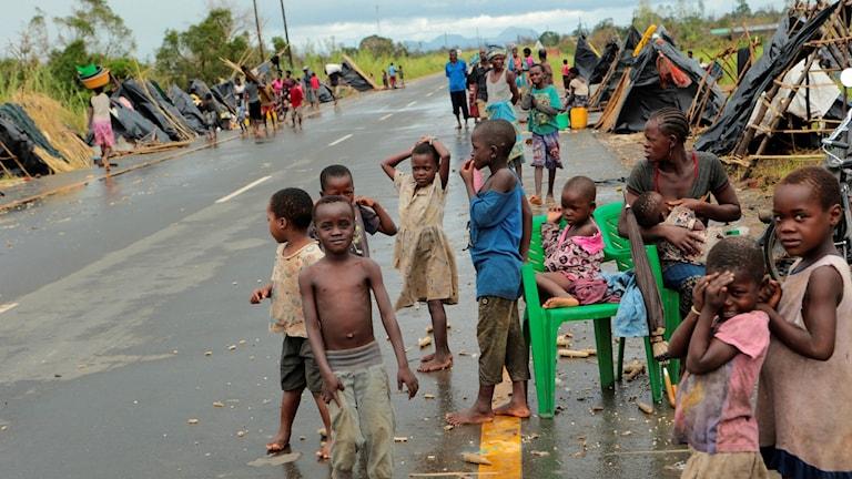 Överlevande från cyklonen Idais framfart samlas vid en väg, utanför staden Beira.