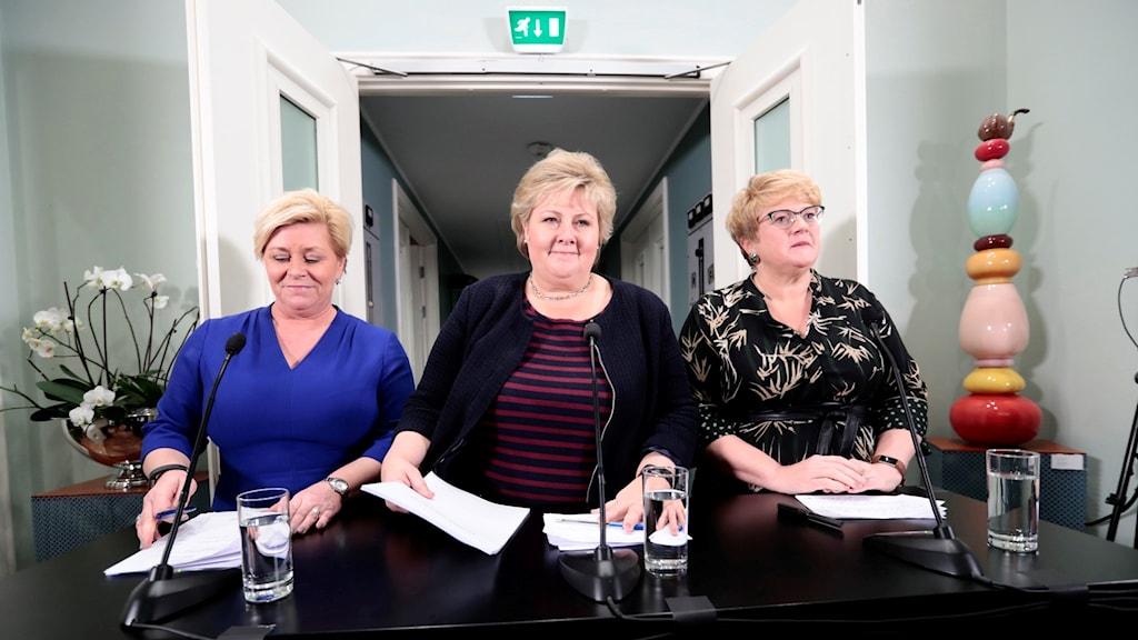 Tre korthåriga blonda kvinnor står vid ett mikrofonförsett bord.