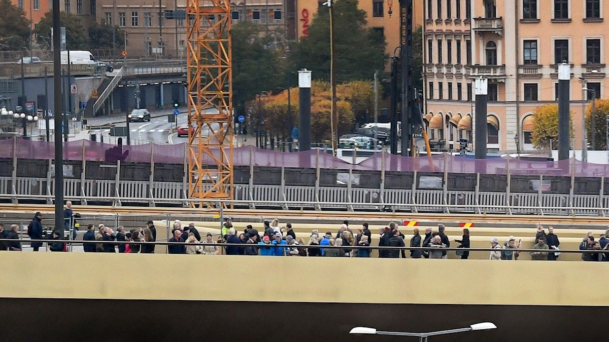 Personer går på en bro som är guldfärgad.