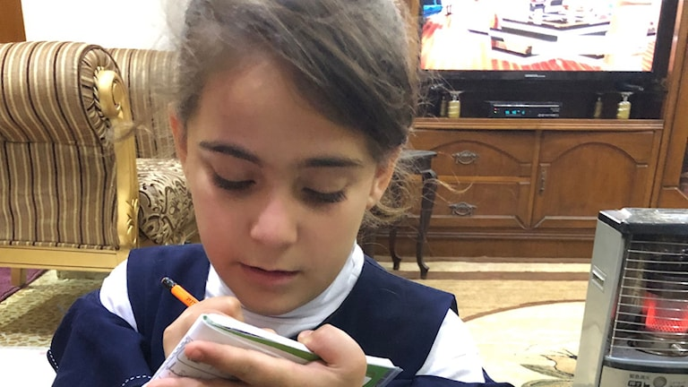 8-åriga Mariam, vars familj flyttade tillbaka för två månader sedan, sitter på golvet intill kaminen och gör läxan