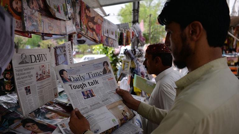 Män läser tidningar.