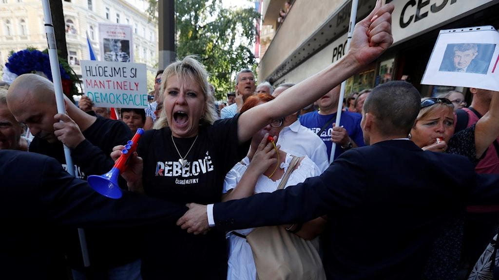 En säkerhetsvakt håller tillbaka en protesterande kvinna med en megafon i handen.