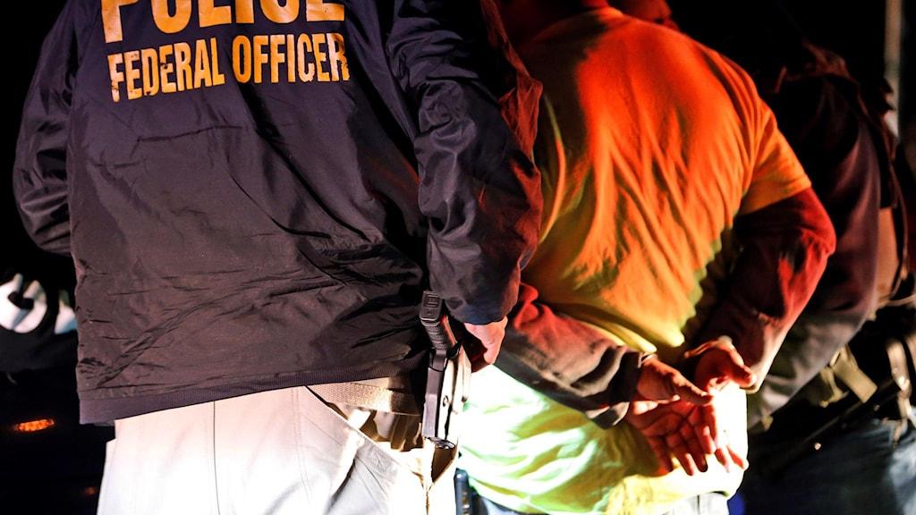 Amerikansk polis jämte man i handfängsel