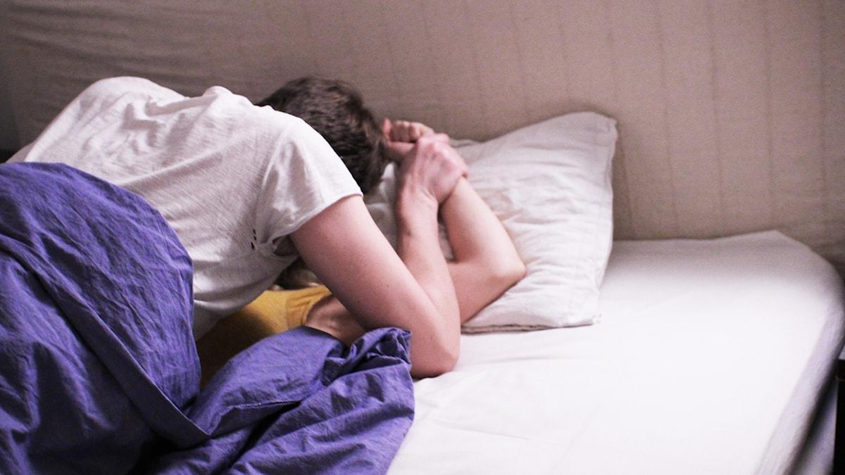 Man håller ner en kvinnas arm mot en kudde.
