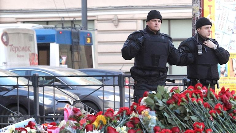 Poliser utanför tunnelbanan i St Petersburg där det ligger drivor av blommor till minne för offren.