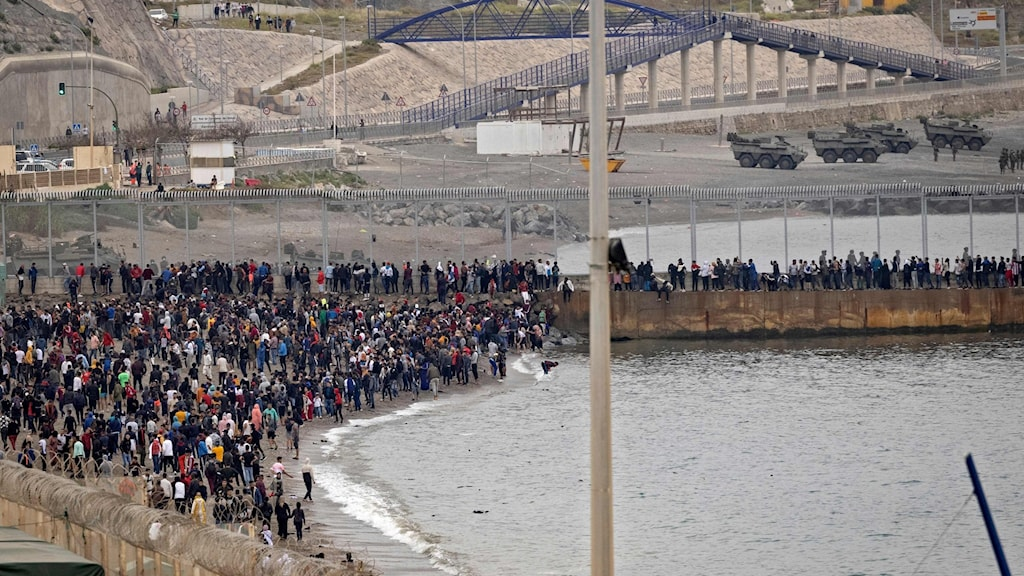 En stor mängd människor vid strandkant och höga staket som utgör gränsen till Spanien.