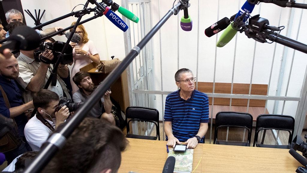 En person sitter i en rättssal med journalister omkring.