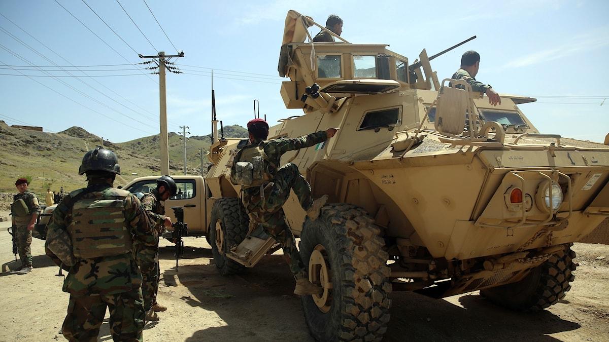 En stridsvagn med personer som är uppe på vagnen.