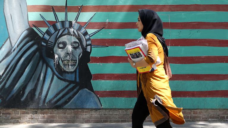 En kvinna passerar en målning på muren omkring den tidigare USA-ambassaden i Teheran. Foto: Atta Kenare/TT.